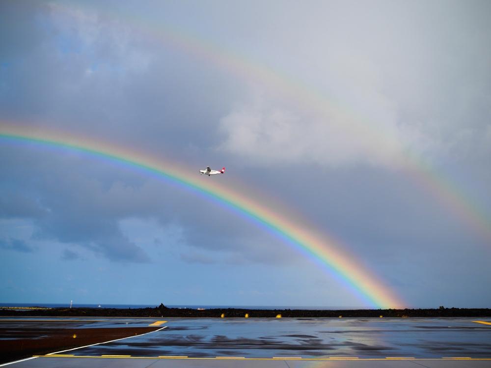 Interisland aircraft flying between two rainbows